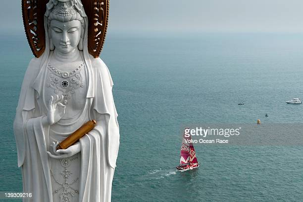CAMPER with Emirates Team New Zealand skippered by Chris Nicholson from Australia sails past the Guan Yin of the South Sea of Sanya at the start of...