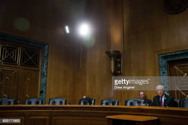 With empty seats of Democrats at to his right Senator and committee chairman Orrin Hatch during a meeting of the Senate Finance Committee to vote on...