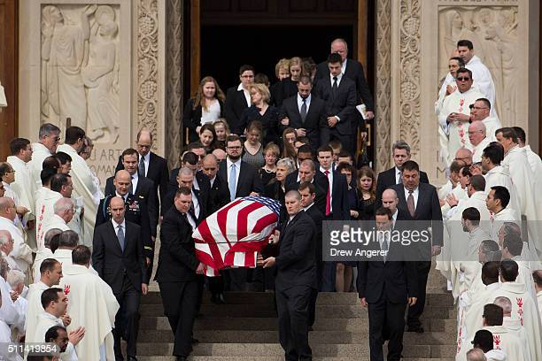 With family members following behind pallbearers carry the casket of late Supreme Court justice Antonin Scalia down the steps of the Basilica of the...