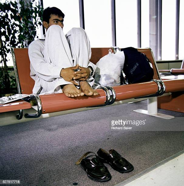 With feet up on airport seating a migrant worker awaits his homeward flight from Bahrain to SouthAsia Sitting with legs gathered and with shoes...