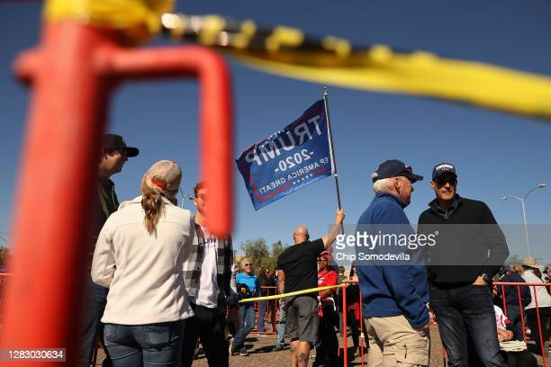 With few face masks and no social distancing to reduce the risk posed by the coronavirus, supporters wait in line to attend a campaign rally with...