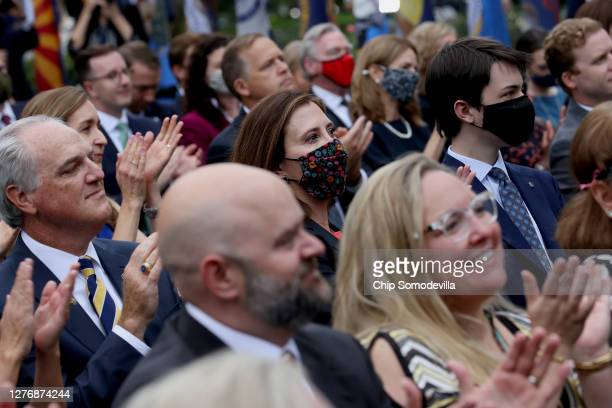 With few wearing masks to protect against the coronavirus, guests applaud President Donald Trump as he introduces 7th U.S. Circuit Court Judge Amy...