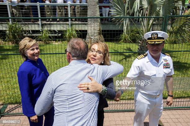 With former Secretary of State Hillary Clinton on one side and her husband Captain Mark Kelly on the other side Gabrielle Giffords greets a well...