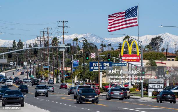With fresh snow on the San Gabriel mountains in the background and Santa Ana winds blowing throughout Orange County a large America flag stands out...