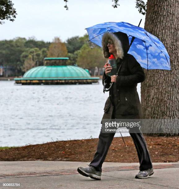 With frigid temperatures blanketing most of the country a pedestrian in Lake Eola Park bundles up against the chill in Orlando Fla on Tuesday Jan 2...