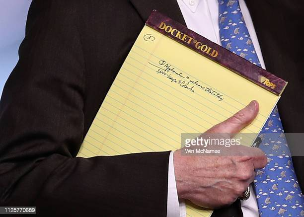 With handwritten notes on a legal pad, National Security Advisor John Bolton listens to questions from reporters during a press briefing at the White...