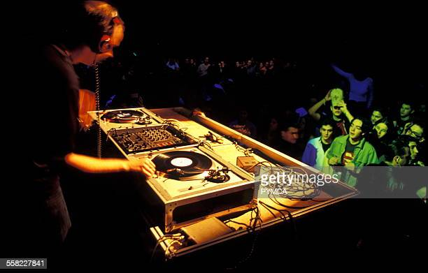 A DJ with headphones on plays to a crowd using turntables London UK 1990s