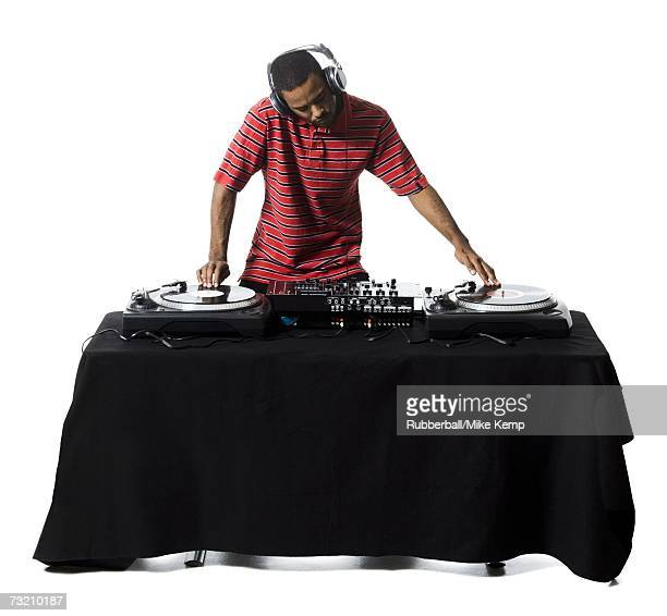 dj with headphones spinning records - dj stock pictures, royalty-free photos & images