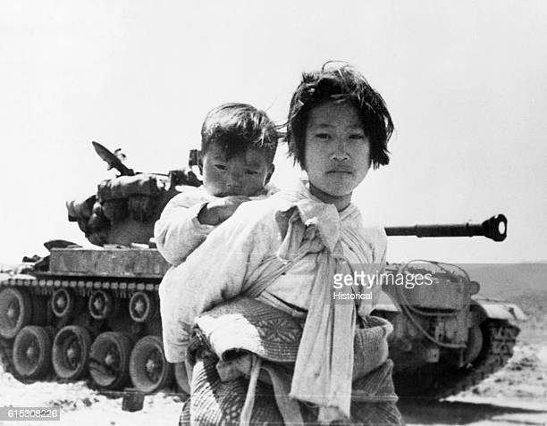 With her brother on her back a war weary Korean girl tiredly trudges by a stalled M26 tank at Haenju Korea June 9 1951 | Location Haenju Korea