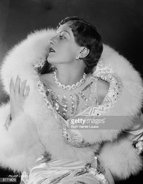 With her hair cut short, film star Joan Crawford wears a jewelled and embroidered evening wrap edged with swansdown and a jewelled choker necklace.