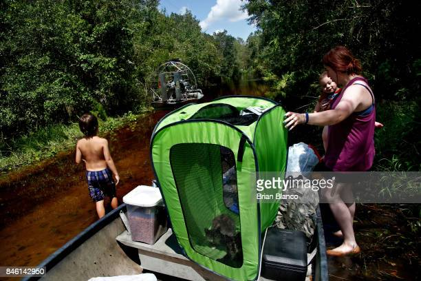 With her home surrounded by floodwater from the nearby Peace River Robyn Barber waits in the boat with her two children her cats and everything they...