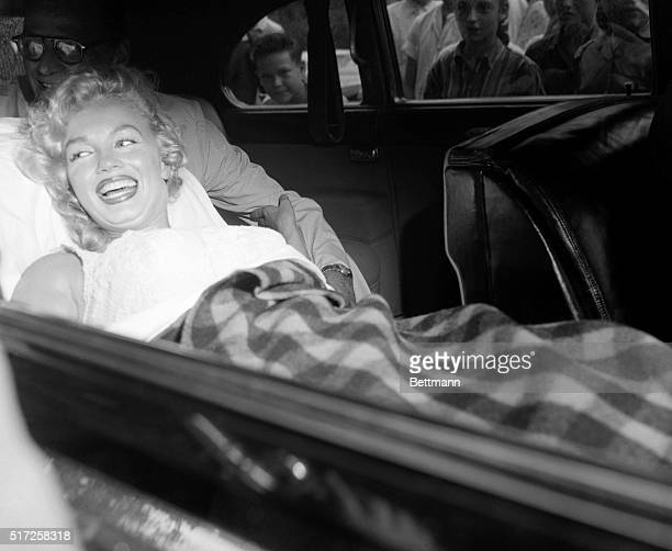 With her playwright husband, Arthur Miller, seated behind her, actress Marilyn Monroe smiles happily and waves to admirers as she drives home from...