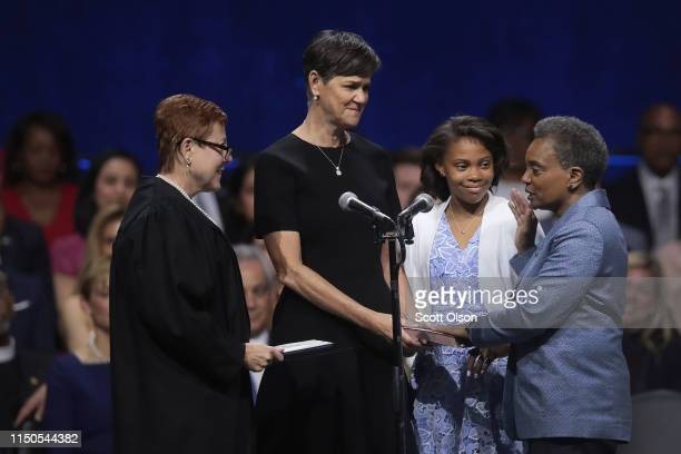 With her wife Amy Eshleman and daughter Vivian by her side Lori Lightfoot is sworn in as Mayor of Chicago by Judge Susan Cox during a ceremony at the...