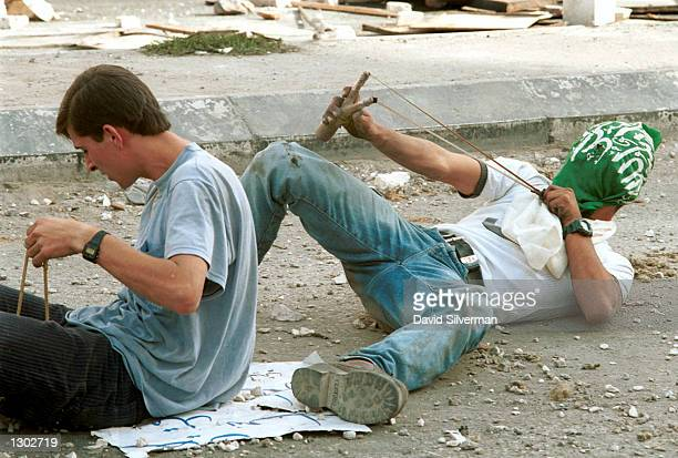 With his face masked by an Islamic flag a Palestinian lies on his back to improve his angle as he fires stones with a slingshot October 17 2000 at...