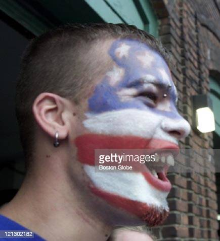 With his face painted like an American Flag Chris Fisher from Abington calls to a friend outside Fenway Park