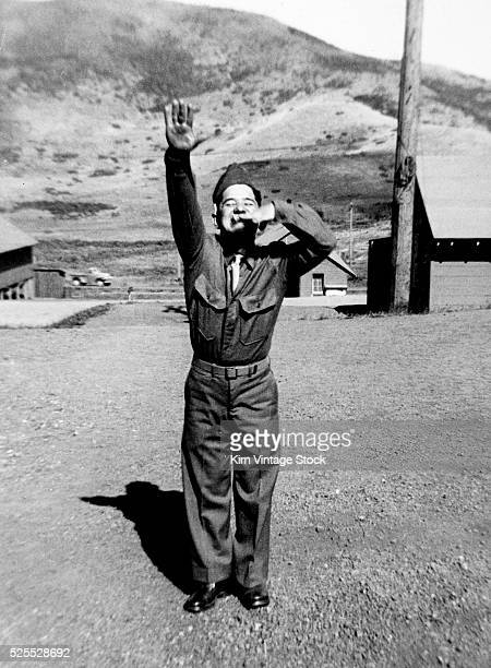 With his finger as a mustache and performing a Nazi salute an American soldier plays the role of Adolf Hitler during World War II