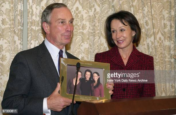 With his former wife Susan Brown smiling at his side Mayor Michael Bloomberg holds a photo of her and their daughters Emma and Georgina They were on...
