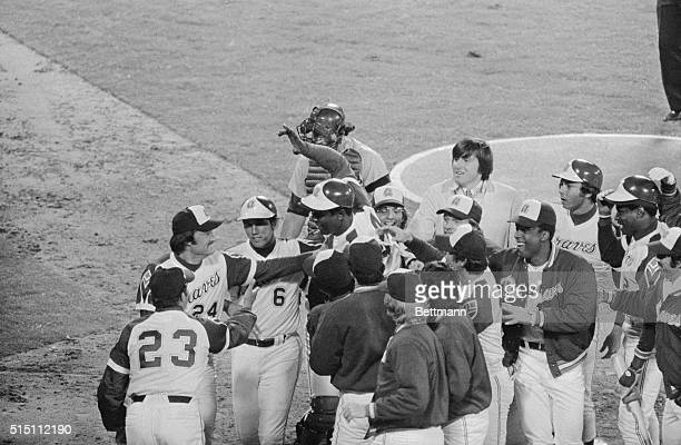 With his hand held aloft Hank Aaron leaps into a host of cheering teammates after he hit his 715th home run on April 8th during the night of breaking...