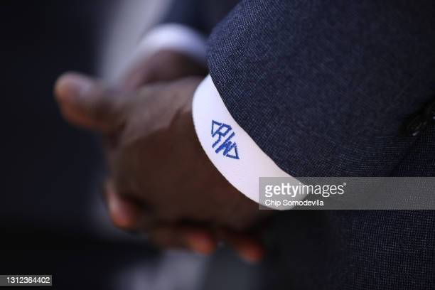 With his initials on his sleeve, Sen. Raphael Warnock and fellow Congressional Black Caucus members talk to reporters following a meeting with U.S....