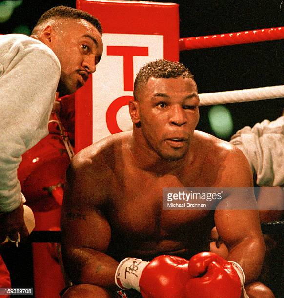 With his left eye closed American boxer Mike Tyson prepares to come out for the seventh round during his world heavyweight title fight against James...