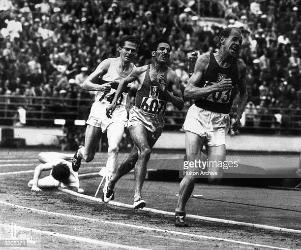 With his trademark grimace Emil Zatopek of Czechoslovakia charges to the lead entering the homestretch of the 5000 meters final at the 1952 Olympic...