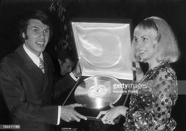 With his wife Nicole Belgian singersongwriter Salvatore ADAMO displays the Gold Album he has just received from Mr MINCHIN the CEO of PATHEMARCONI