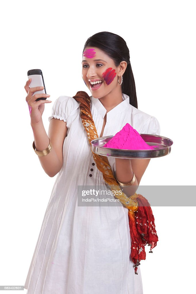 WOMEN with holi colour reading an sms on mobile phone : Stock Photo