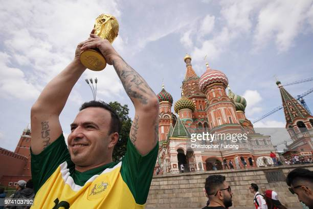 With hours to go until the first World Cup game between Russia and Saudi Arabia an Australian fan holds his own trophy in the air in near Red Square...