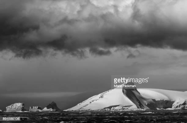 ANTARCTICA COASTLINE with icebergs with dark cloud in sky.