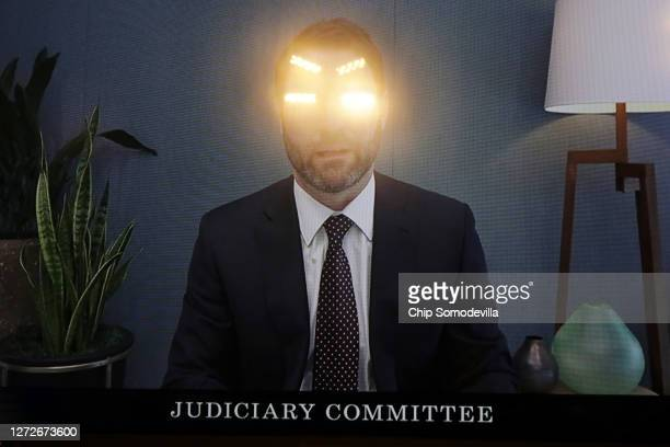 With lights reflected in the television, Google President for Global Partnerships and Corporate Development Donald Harrison testifies via live video...