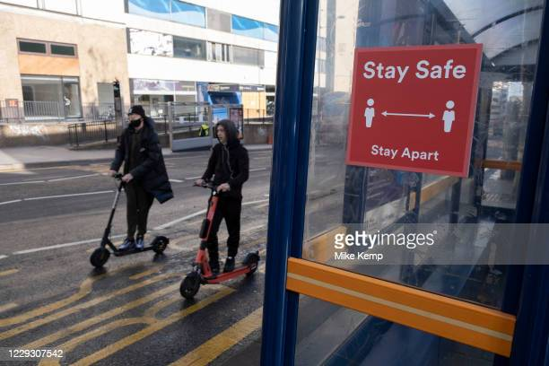 With local coronavirus lockdown measures in place and Birmingham currently set at 'Tier 2' or 'high', young men on e-scooters pass bus stops in the...