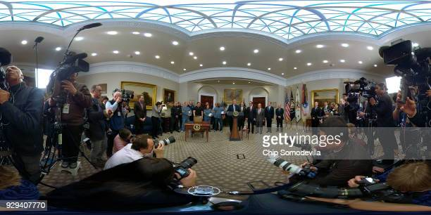With members of his economic team and steel and aluminum workers standing by US President Donald Trump delivers remarks before signing the 'Section...
