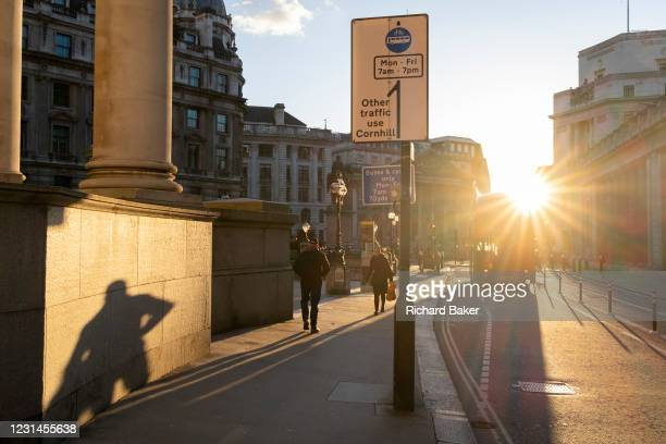 With most Londoners still working from home, a commuter leaves their shadow on a wall of Royal Exchange while walking along a quiet Threadneedle...
