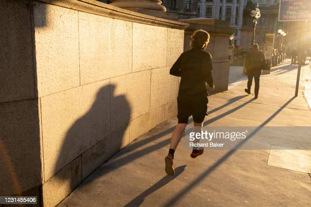 With most Londoners still working from home, a runner leaves his shadow on a wall of Royal Exchange while walking along a quiet Threadneedle Street...