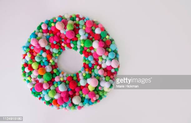 christmas wreath with multi-colored pom poms. - pom pom stock pictures, royalty-free photos & images