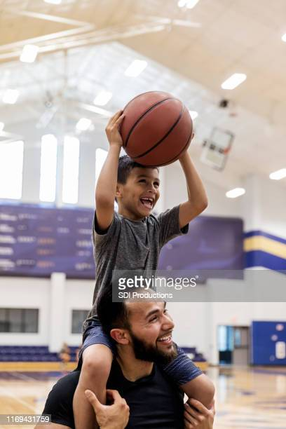 with nephew on uncle's shoulders, both have fun shooting baskets - estilo de vida ativo imagens e fotografias de stock
