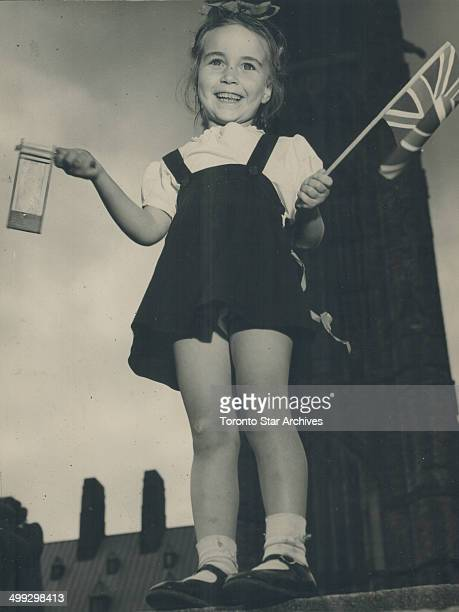 With Noisemaker and Union Jack this cute Ottawa youngster celebrated VE Day on Parliament Hill Where she heard Acting Prime Minister J L Ilsley speak
