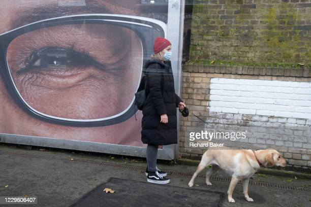 With one eye from half of a Specsavers billboard ad, a dog owner stands with a labrador on the platform of Denmark Hill Station in south London, on...