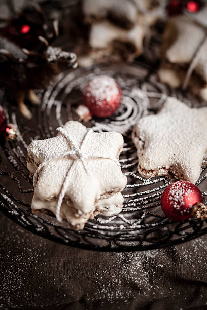 With powdered sugar sprinkled star-shaped cinnamon cookies and red Christmas baubles on cake stand