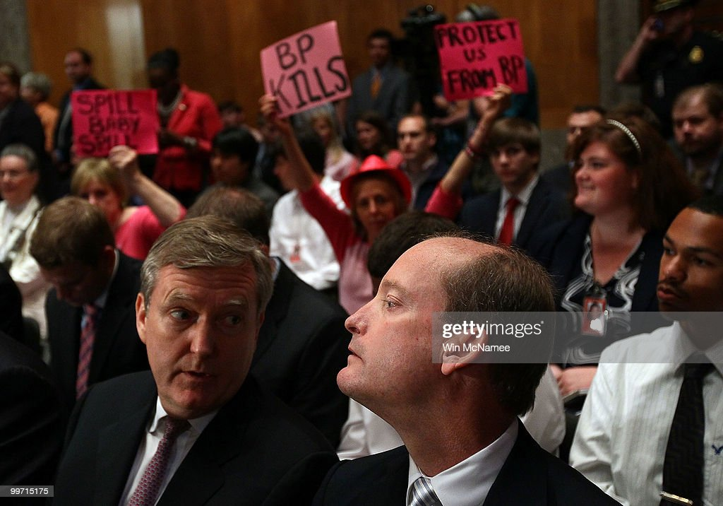 With protesters behind him, BP America Chairman and President Lamar McKay (R) waits in the audience to testify before the Senate Homeland Security and Governmental Affairs Committee May 17, 2010 in Washington, DC. McKay, Homeland Security Secretary Janet Napolitano and Coast Guard Deputy National Incident Commander Rear Adm. Peter Neffenger were scheduled to testify on the topic of 'Gulf Coast Catastrophe: Assessing the Nation's Response to the Deepwater Horizon Oil Spill.'