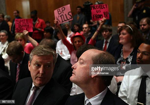 With protesters behind him BP America Chairman and President Lamar McKay waits in the audience to testify before the Senate Homeland Security and...