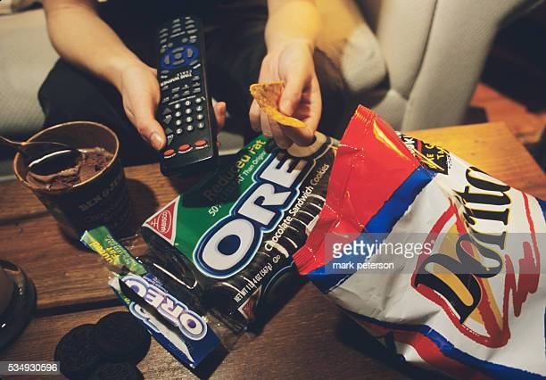 With remote control in one hand and nacho chip in the other a teenager eats the food she likes in front of the TV