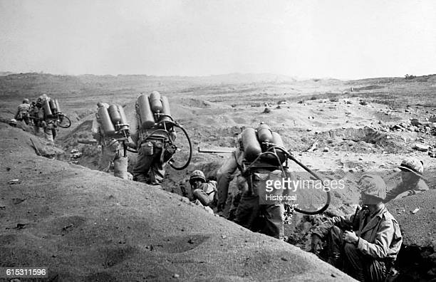 With riflemen leading the way flame throwing US Marines bent by the weight of their weapons move forward toward enemy pillboxes on Iwo Island...
