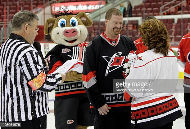With Ron the Ref Biscotti left presiding and Carolina Hurricanes mascot Stormy left center serving as ringbearer Alain Taylor right center and Monica...