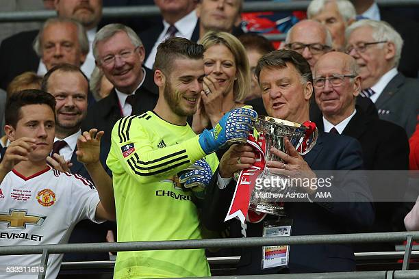 LONDON ENGLAND MAY 21 With Sir Alex Ferguson watching goalkeeper David de Gea of Manchester United gives the FA Cup trophy to Louis van Gaal Manager...