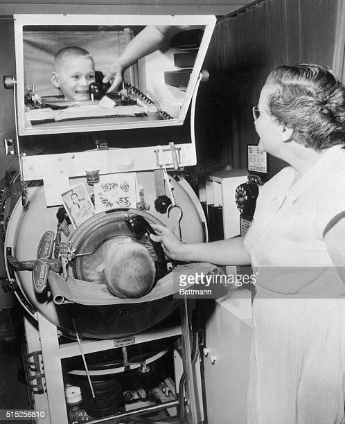 With souvenirs and getwell cards attached to his iron lung 6 year old Tracy Hamilton of Firebaugh California smiles gleefully as he talks by...