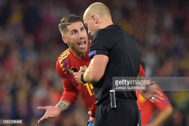 With Spain's defender Sergio Ramos argues with Polish referee Szymon Marciniak during the UEFA Nations League football match between Spain and...