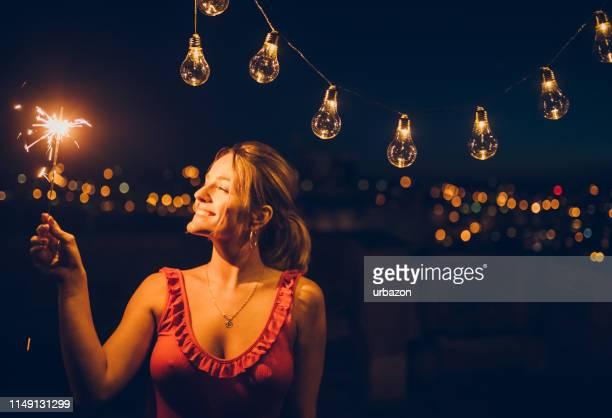 with sparkler on the rooftop - decote imagens e fotografias de stock
