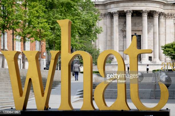 With St Paul's Cathedral in the distance, the philosophical pronoun word 'What' is in the foreground on Peter's Hill in the City of London, the...