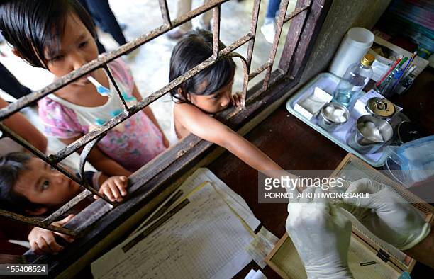 with story HEALTHMALARIATHAILANDMYANMAR BY Dan Rook A Thai Health official performs a blood test on children at a Malaria clinic in Kanchanaburi...